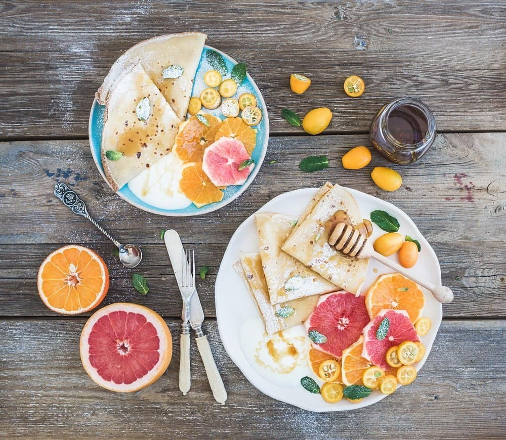 Spring vitamin breakfast set. Thin crepes or pancakes with fresh grapefruit, orange, kumquat, honey, cream and mint leaves over a rustic wood background
