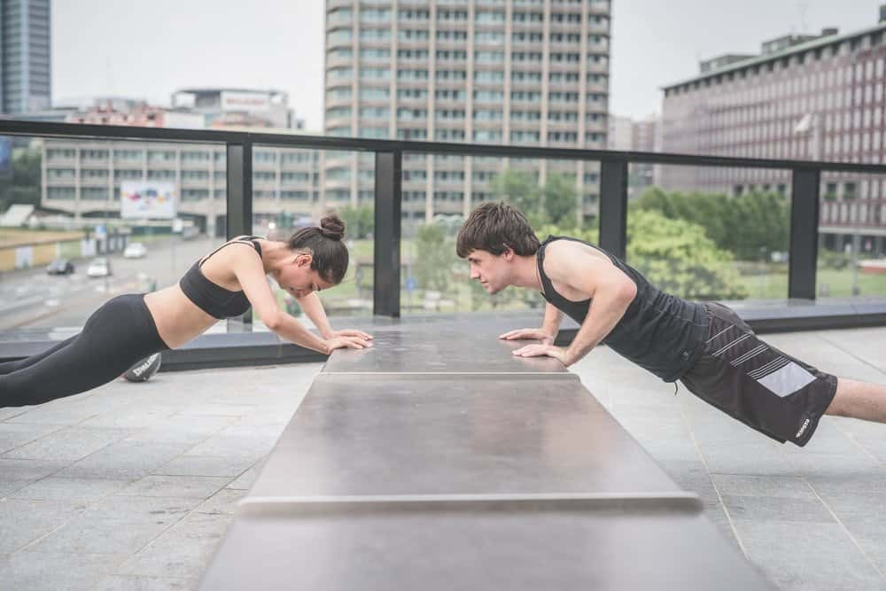 Couple of young handsome caucasian sportive man and woman doing push-ups, facing each other - sportive, fitness, healthy, training concept - HIIT for Weight Loss Training