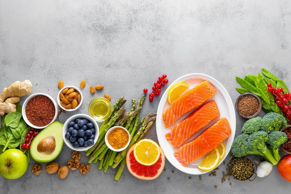 Healthy food background, salmon fish, spinach, quinoa, apple, blueberry, asparagus, turmeric, red currant, broccoli, mung bean, walnuts, grapefruit, ginger, avocado, almond, and green peas, top view
