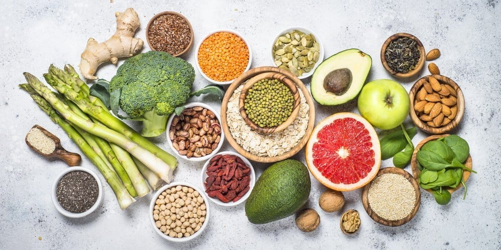 Superfoods. Organic food and healthy vegan food. Legumes, nuts, seeds, fruit and vegetables. Top view.
