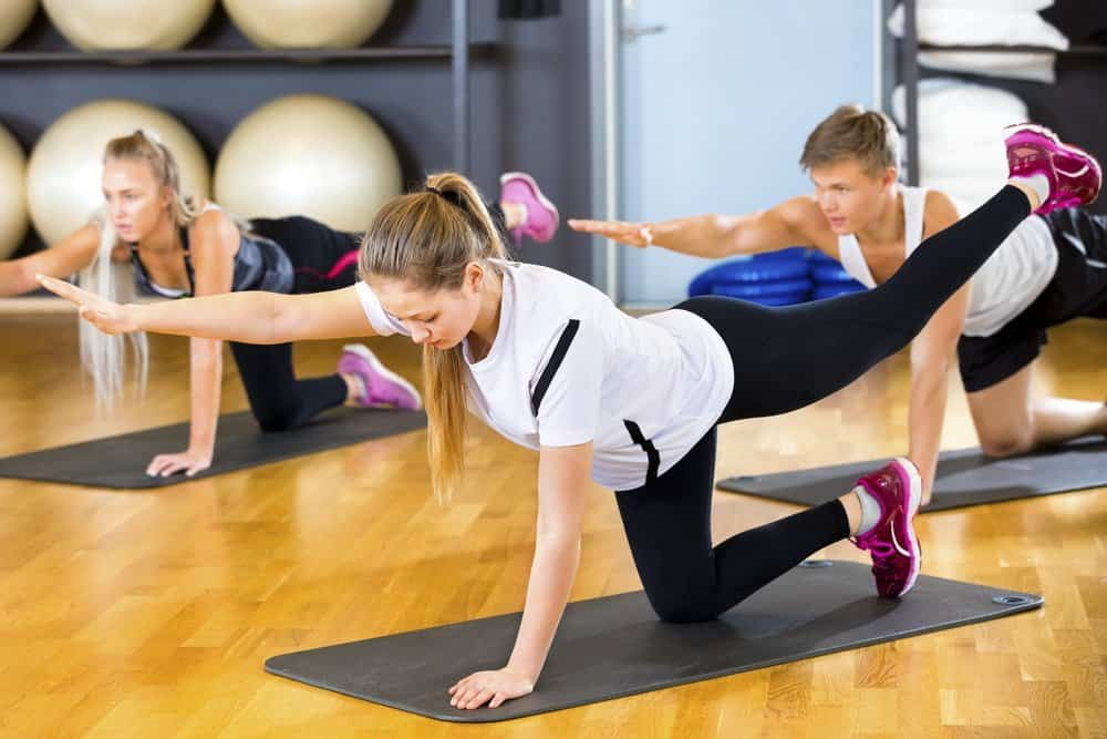 Young woman in sportswear exercising with friends on mats at fitness center - HIIT for Weight Loss Training