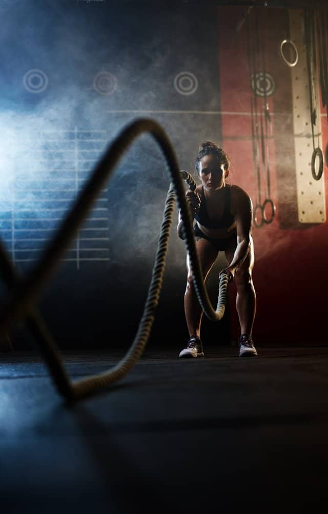 Sporty woman working out with ropes in gym - HIIT for Weight Loss Training