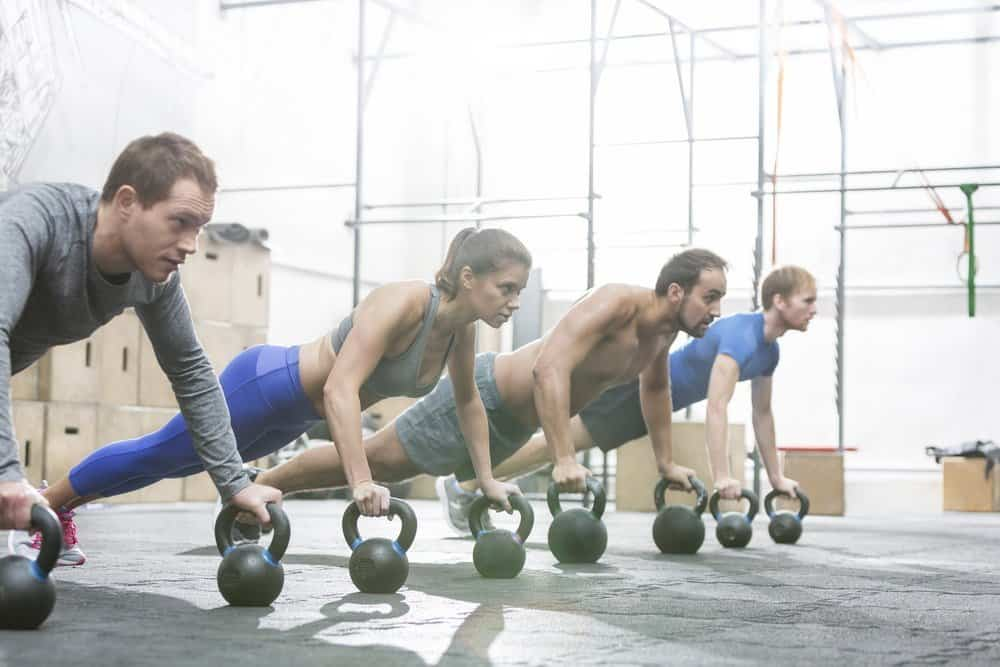 Dedicated people doing pushups with kettlebells at crossfit gym - Top 10 Fitness Trends of 2019
