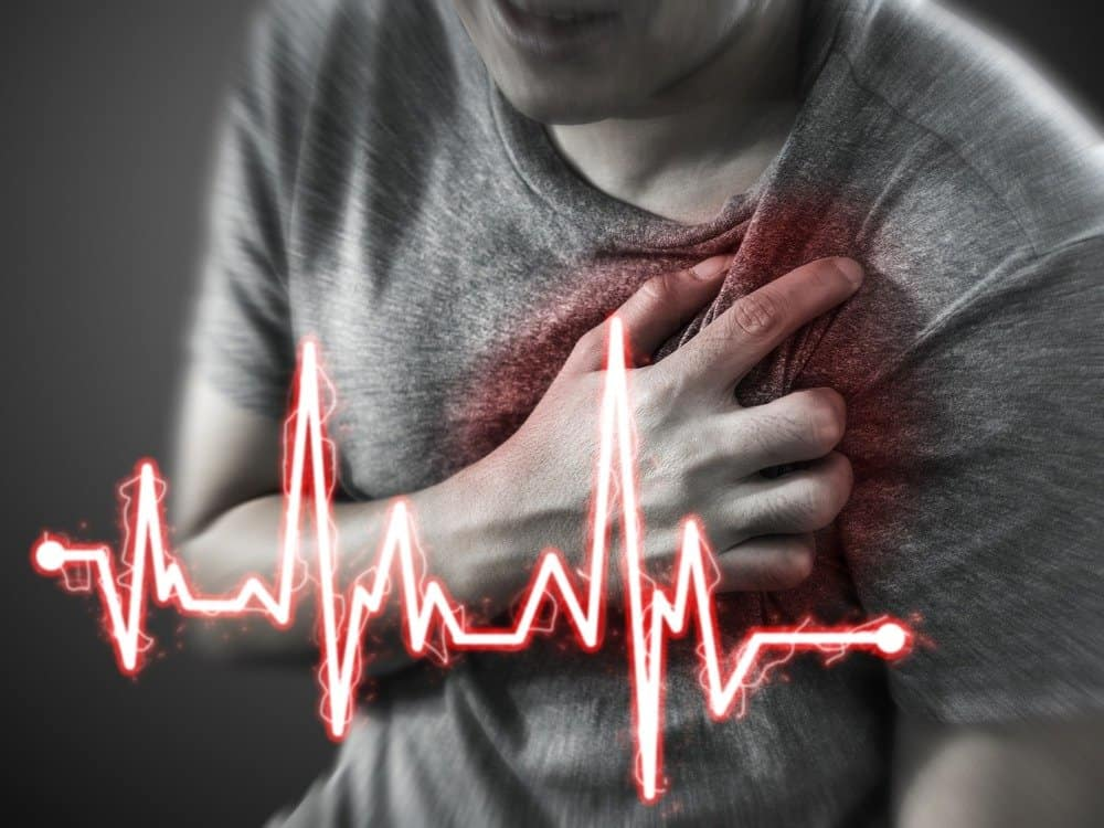 Severe heartache, man suffering from chest pain, having heart attack or painful cramps, pressing on chest with painful expression - Does Exercise Make You Live Longer?