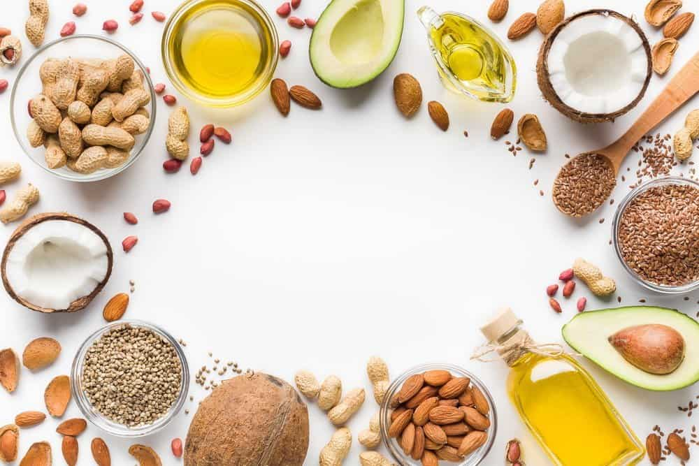 Avocado, coconut, almonds, hemp seeds, linseeds, olives and oils over white background, top view. Alternative oils concept, copy space - Diet Smoothies for Weight Loss