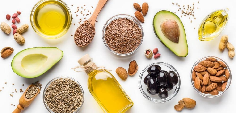 Avocado, almonds, hemp seeds, linseeds, olives and oils over white background, top view. Alternative oils concept - Side Effects from Keto Diet