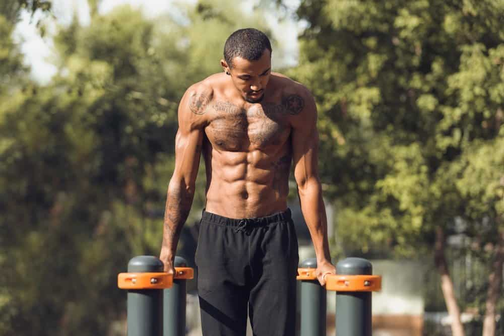 Athletic naked man doing push ups on parallel bars outdoors - Top 10 Fitness Trends of 2019