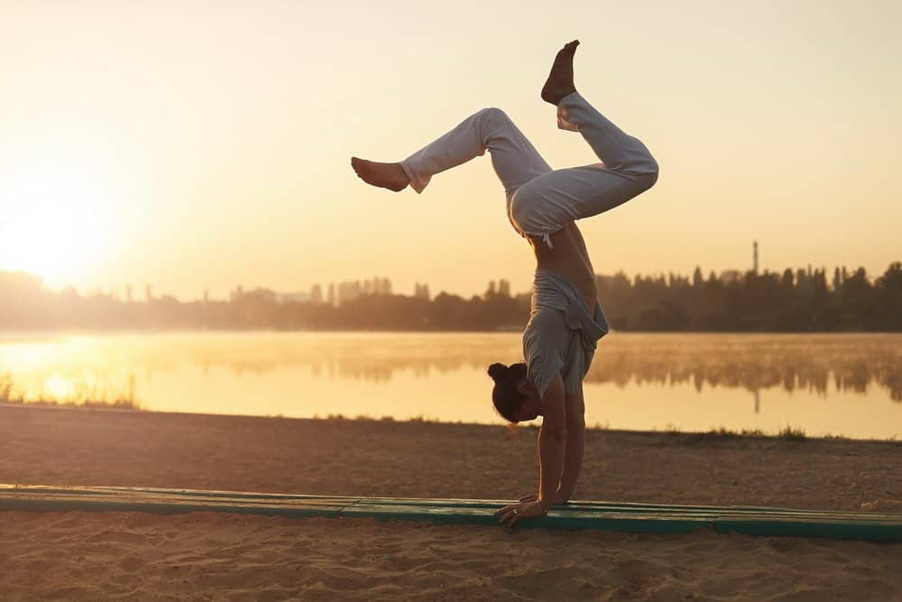 Concept about lifestyle and sport. Capoeira on the beach, near lake one performer, at sunrise. Athletic man in white pants standing on arms upside down while workout in the park in the heart of city. - A Natural Way to Detox Your Body