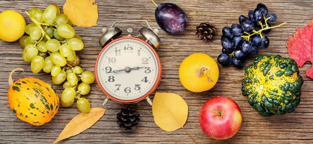 Autumn background with clock,pumpkin, apples and grapes.Autumnal concept.Harvesting
