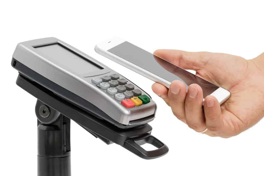 Male hand use smartphone for contactless payment with nfc techology. Side view isolated on white background - Benefits in Wearable Technology