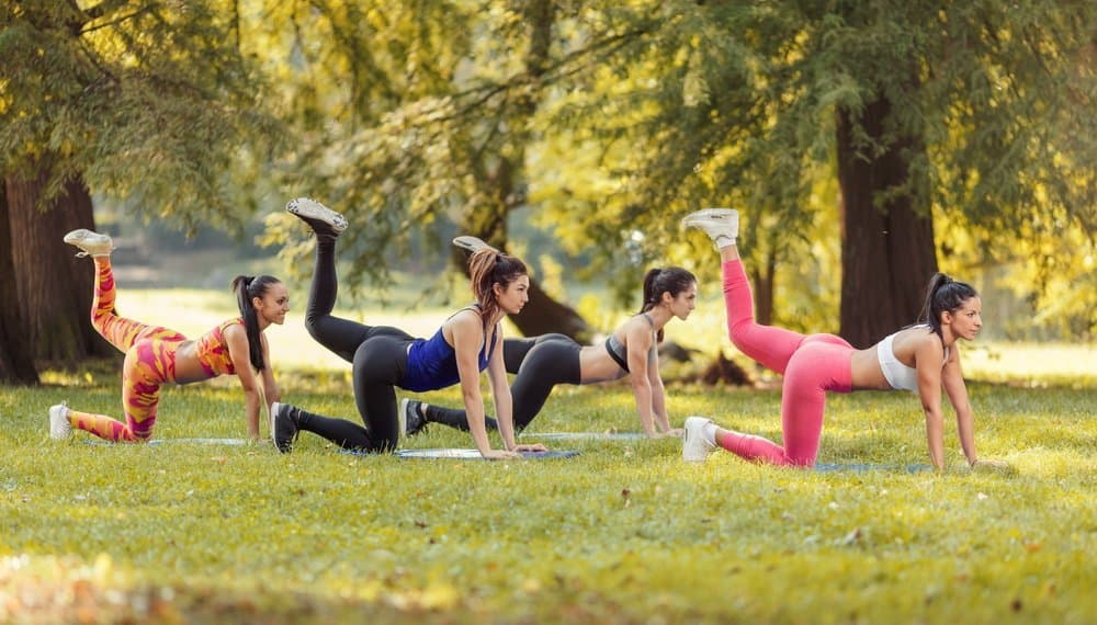 Four beautiful female friends doing exercise in the park. - Diet Smoothies for Weight Loss