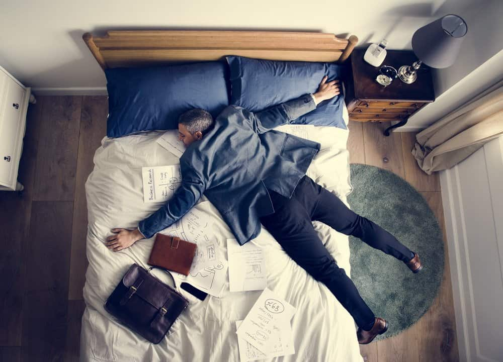 Exhausted business man falling asleep as soon as he came back home