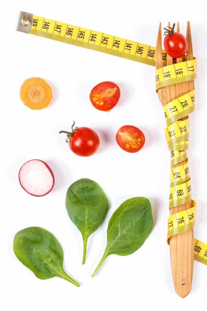 Tips on Lose Weight Quickly - Wooden fork wrapped in tape measure and fresh ripe vegetables on white background, concept of lose weight and healthy nutrition