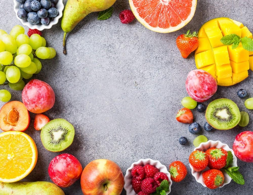 Fresh assorted fruits and berries on light gray background. Colorful clean and healthy eating. Detox food. Copy space. Top view.