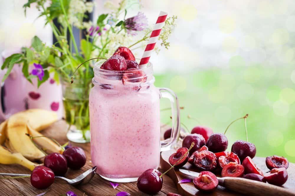 Fresh homemade healthy berry smoothie in mason jar on window background