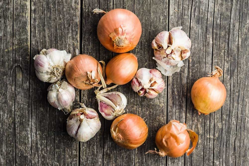 Fresh onion and garlic bulbs on old wooden table. - The Metabolic Reset Diet Plan