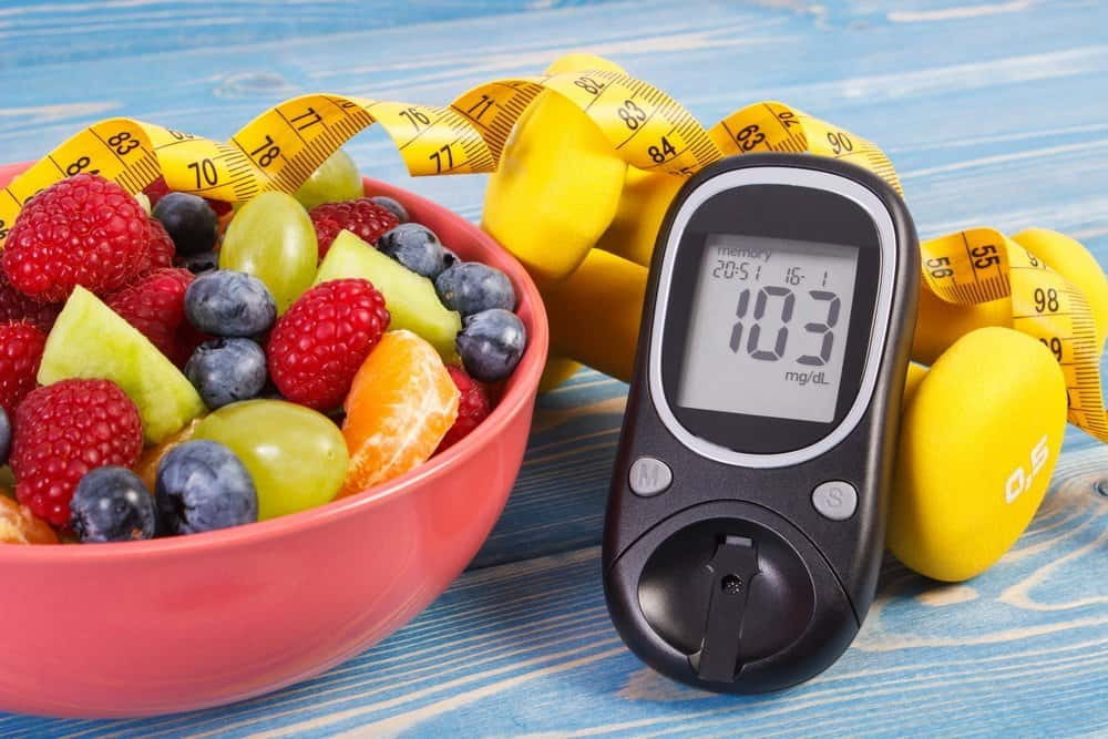Fresh salad, glucose meter with result of sugar level, tape measure and dumbbells for fitness, concept of diabetes, slimming, healthy lifestyles and nutrition