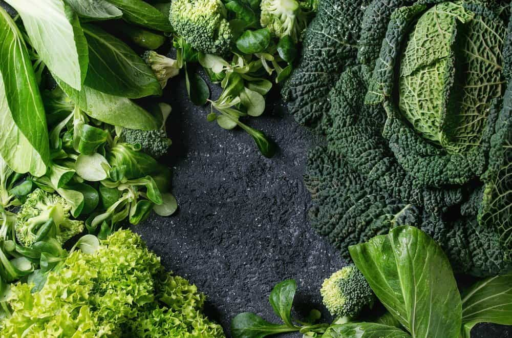 Variety of raw green vegetables salads, lettuce, bok choy, corn, broccoli, savoy cabbage as frame over black stone texture background. Top view, space for text - Diet Smoothies for Weight Loss