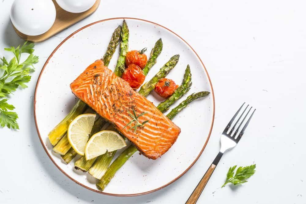 Grilled salmon fish fillet with asparagus and tomato on white craft plate. Top view on white stone table. - Side Effects from Keto Diet