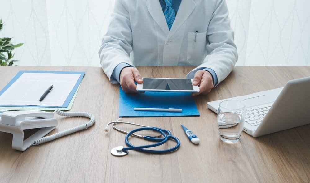 Professional doctor working at office desk, he is using a digital tablet, healthcare and technology concept - Benefits in Wearable Technology