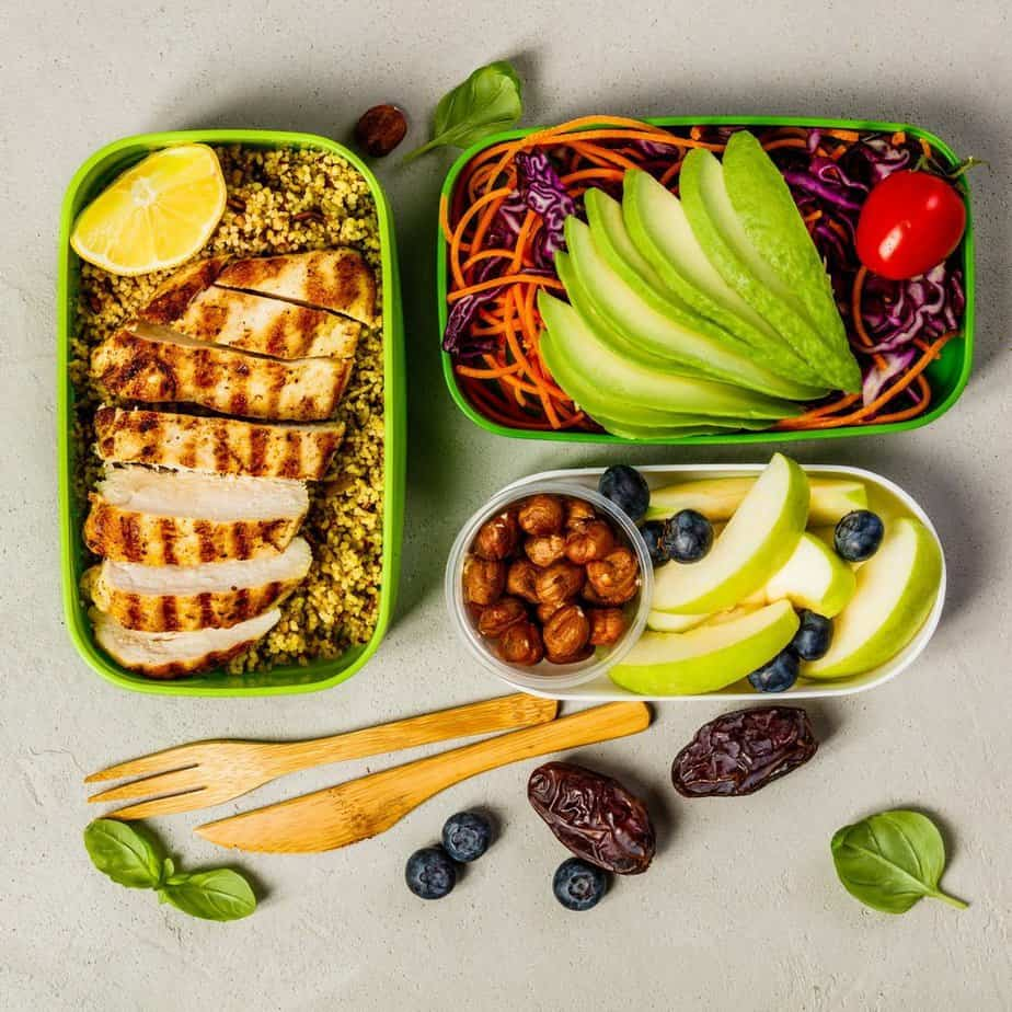 Tips on Lose Weight Quickly - Healthy meal prep containers: Couscous with grilled chicken breast, salad, avocado, berry, apple, nuts and dry dates. Keto, ketogenic diet, low carb, healthy food concept. Top view