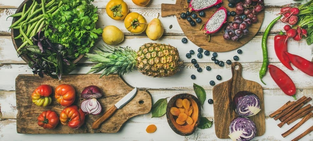 Helathy vegan food cooking background. Flat-lay of Fresh fruit, vegetables, greens and superfoods on boards over white wooden table, top view, wide composition. Clean eating, alkaline diet concept - The Metabolic Reset Diet Plan