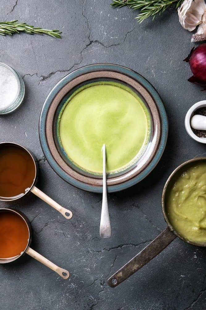 Home made broccoli and pea puree soup decorated with rosemary, thyme, garlic and onions, served with vegetable broth. Top View - The Metabolic Reset Diet Plan