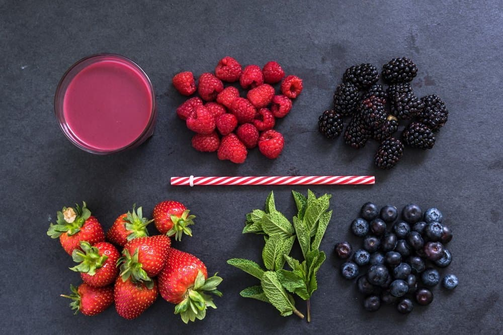 ingredients for perfect berry smoothie, flat lay overhead on dark slate - Diet Smoothies for Weight Loss