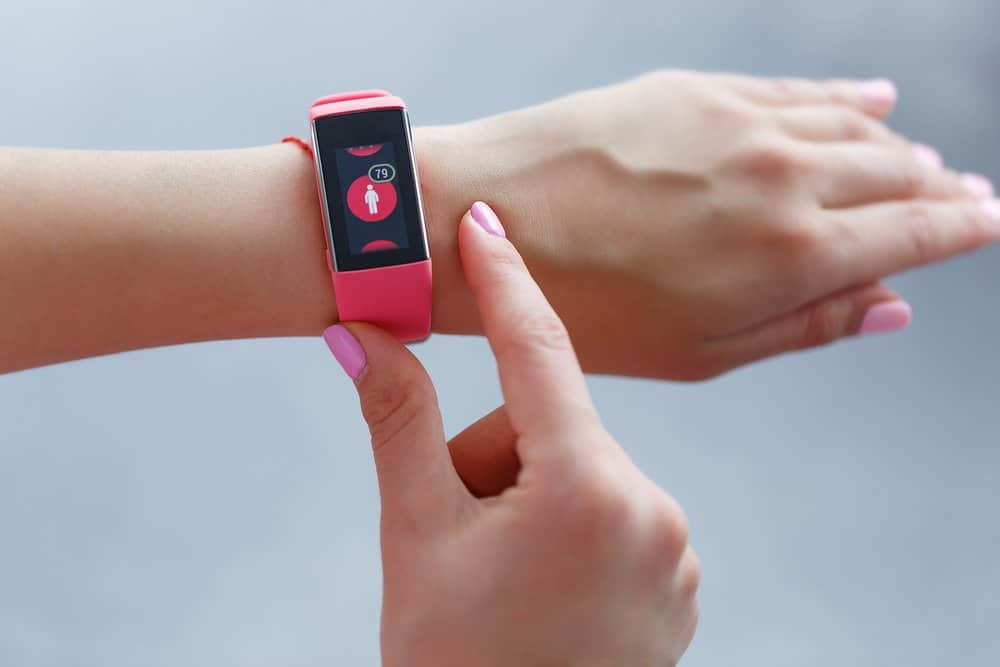 Isolated female hand with pink smartwatch taking pulse after exercising indoor on a light and blured background - Top 10 Fitness Trends of 2019