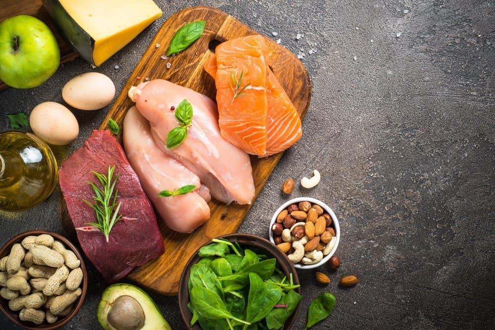Ketogenic low carbs diet. Meat, fish, nuts, oil, cheese, milk and avocado on dark stone background. Top view with copy space. - Side Effects from Keto Diet