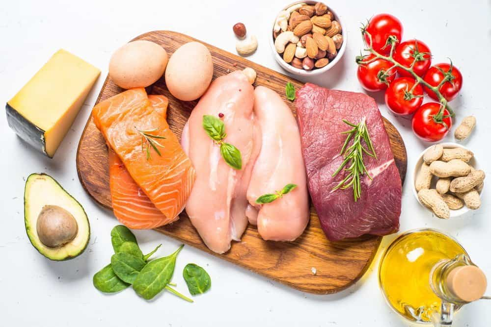 Tips on Lose Weight Quickly - Ketogenic low carbs diet. Meat, fish, nuts, oil, cheese and avocado on white background. Top view.
