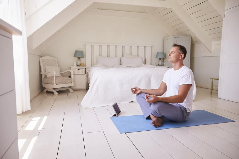 Mature Man With Digital Tablet Using Meditation App In Bedroom - The Metabolic Reset Diet Plan