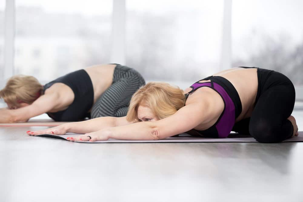 """Fitness, stretching practice, group of two attractive fit mature women working out in sports club, """"warming up"""", doing Frog Yin Yoga Pose, Mandukasana posture in class, full length - Top 10 Fitness Trends of 2019"""