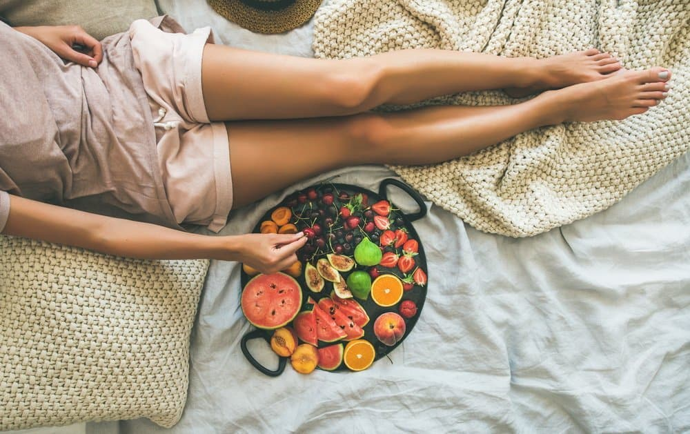 Summer healthy raw vegan clean eating breakfast in bed concept. Young girl wearing pastel colored home clothes taking fruit from tray full of fresh seasonal fruit. Top view, copy space - A Natural Way to Detox Your Body