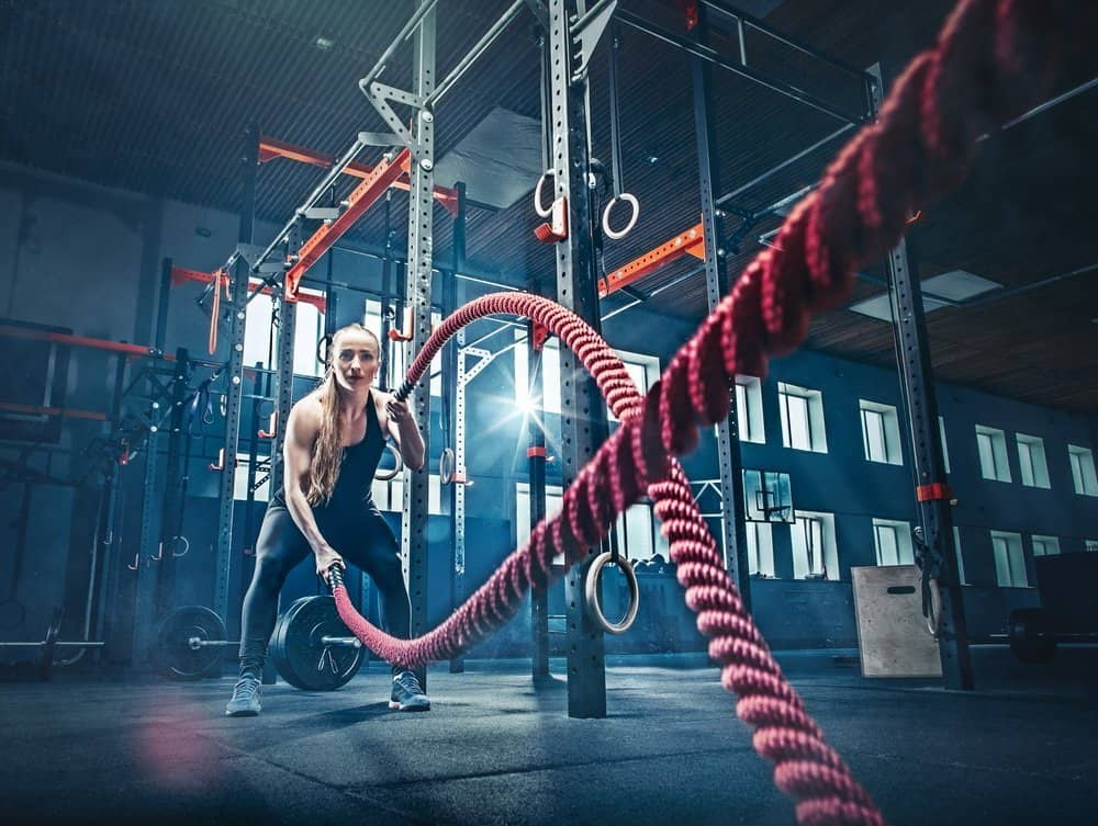 Woman with battle rope battle ropes exercise in the fitness gym. CrossFit concept. gym, sport, rope, training, athlete, workout, exercises concept - Top 10 Fitness Trends of 2019
