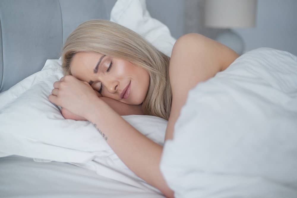 Young beautiful blonde woman sleeping in her bedroom and relaxing in the morning. - A Natural Way to Detox Your Body
