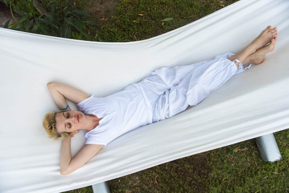 beautiful young woman enjoying free time while resting on white hammock in the backyard
