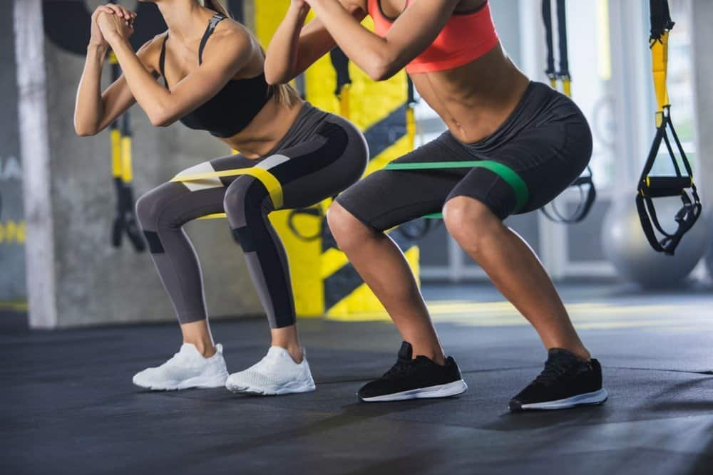 Close up of athletic women in squat together in gym. Couple of fit girls are exercising - How to Motivate Yourself for Workout