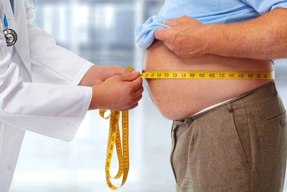 Doctor measuring obese man waist body fat. Obesity and weight loss. - 10 Reasons why Water is Important