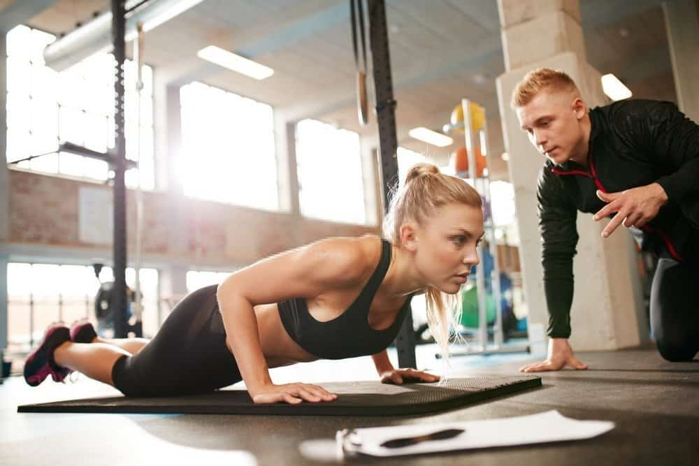 Female exercising with personal trainer at gym - How to Motivate Yourself for Workout
