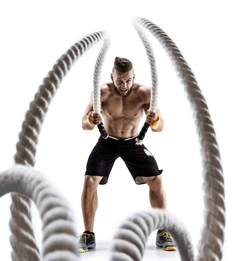 Strength Training Attractive muscular man working out with heavy ropes - 10 Ways to Lose Belly Fat