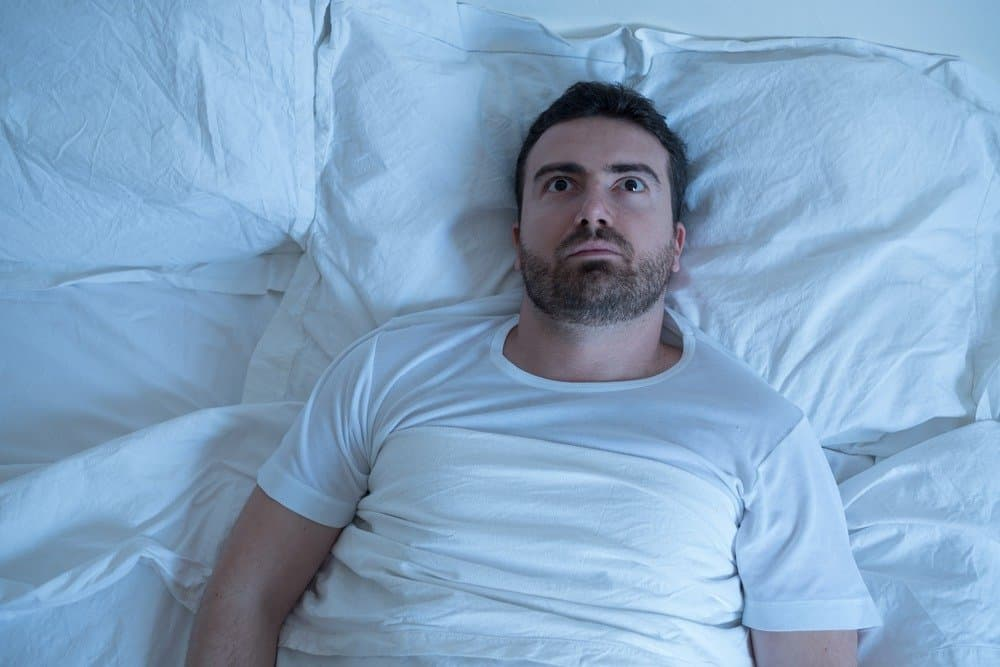 Stressed man trying to sleep in his bed at night - Signs You're Overdoing Cardio