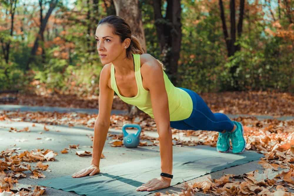 Woman Doing High-Intensity Interval Training Outdoors. High Plank Exercise. Autumn - Low Intensity Interval Training Workout