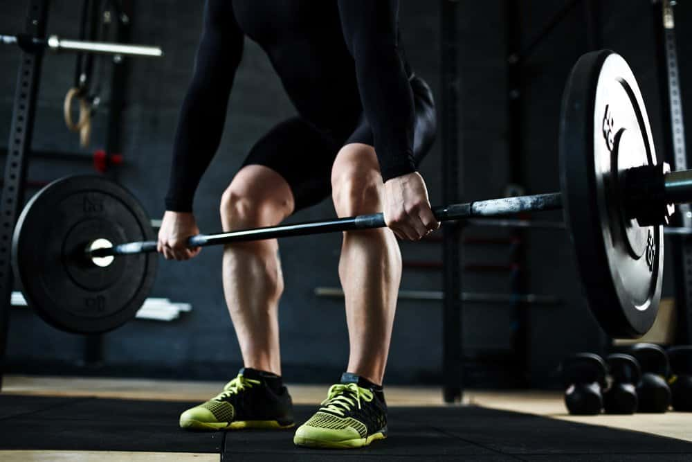 Hands of athlete lifting barbell in gym - Low Intensity Interval Training Workout