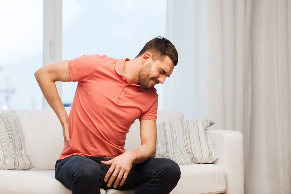 man suffering from backache - Signs You're Overdoing Cardio