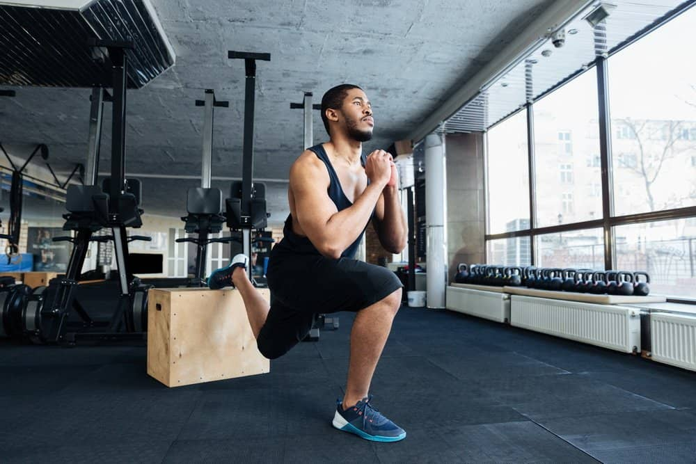 Muscular fitness man doing squats using wooden stand in the gym - Low Intensity Interval Training Workout