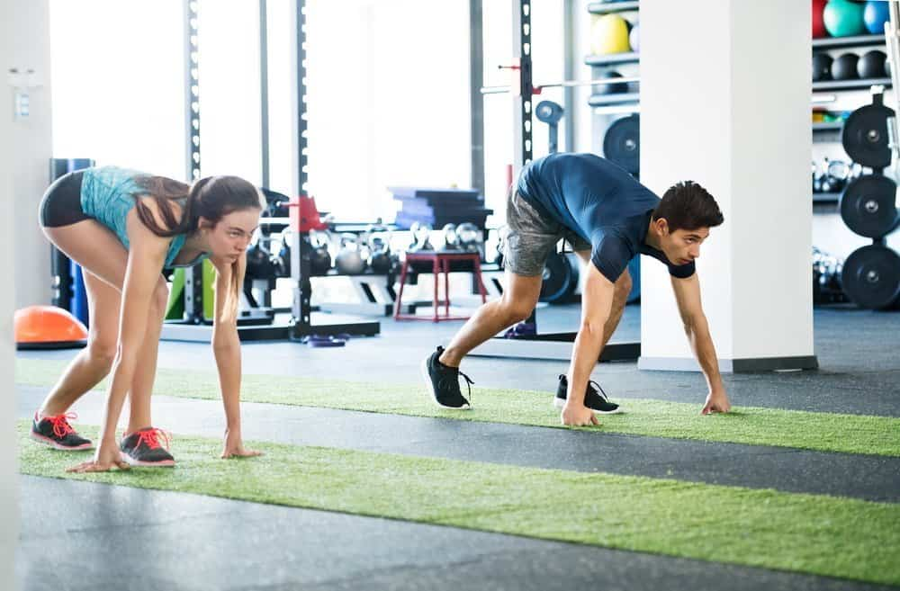 Runners in starting position. Young man and woman prepared for intense training session. Sports training in the gym. - Low Intensity Interval Training Workout