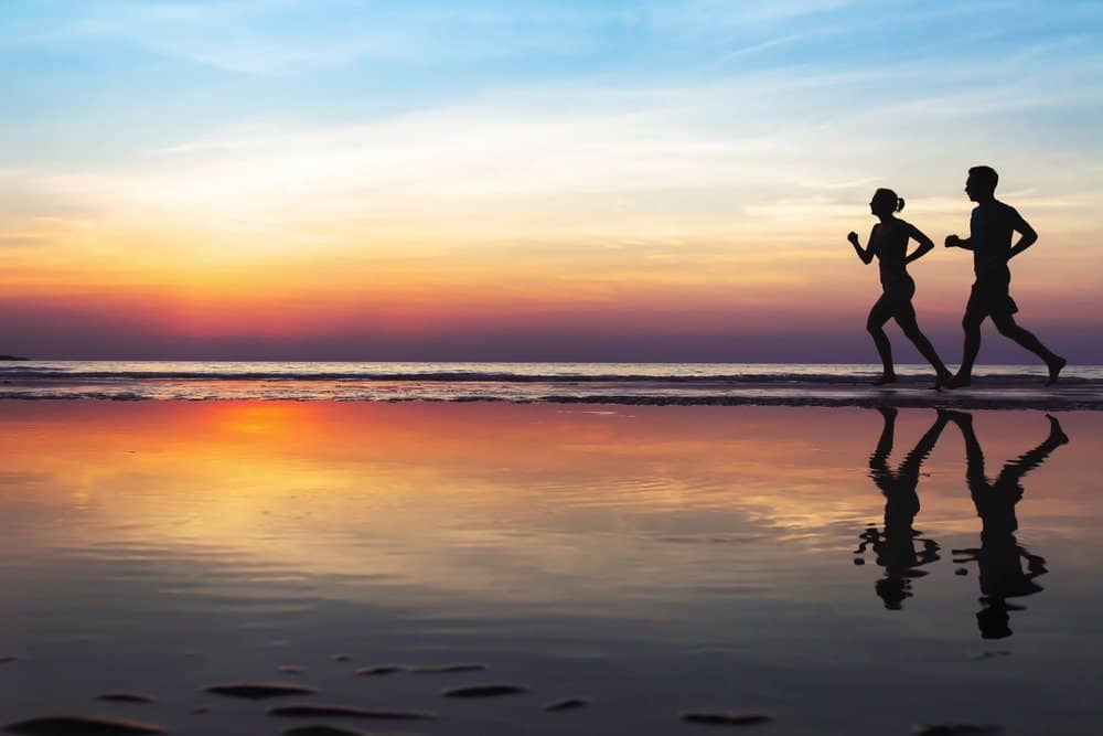 two runners on the beach, silhouette of people jogging at sunset, healthy lifestyle background - How to Motivate Yourself for Workout