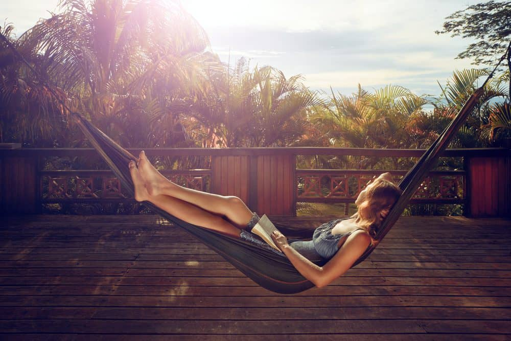 woman with book in her hands is resting in a hammock on the terrace - 10 Ways to Lose Belly Fat