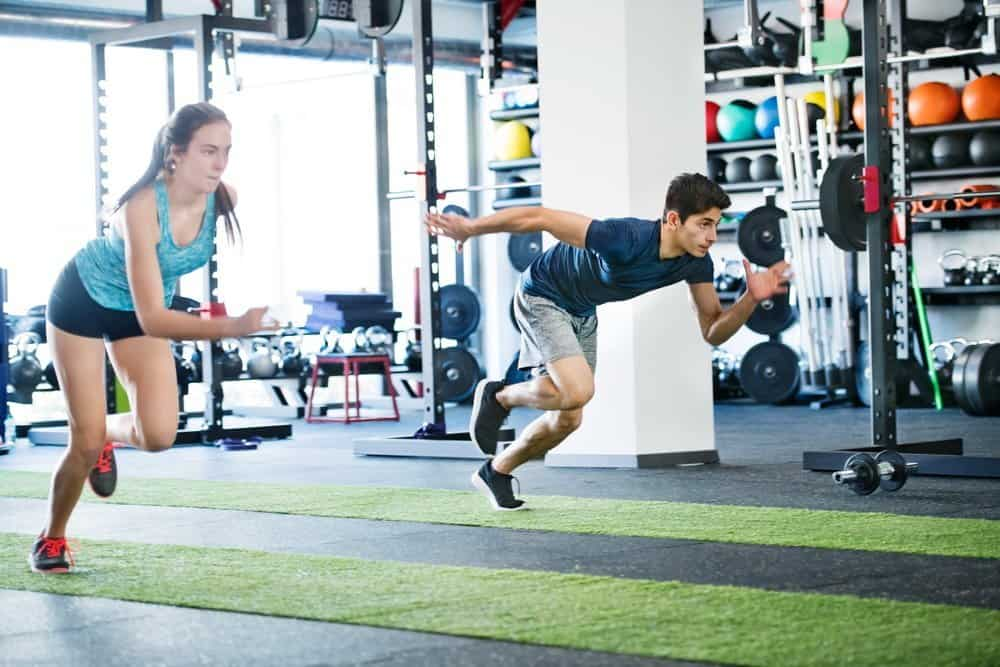 Young fit couple in gym fast running. Young man and woman doing intense training session. Sports training in the gym. - Low Intensity Interval Training Workout